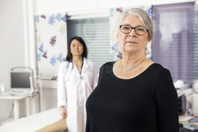 Βέβαιος ανώτερος ασθενής που στέκεται με το γιατρό στο υπόβαθρο στοκ φωτογραφίες