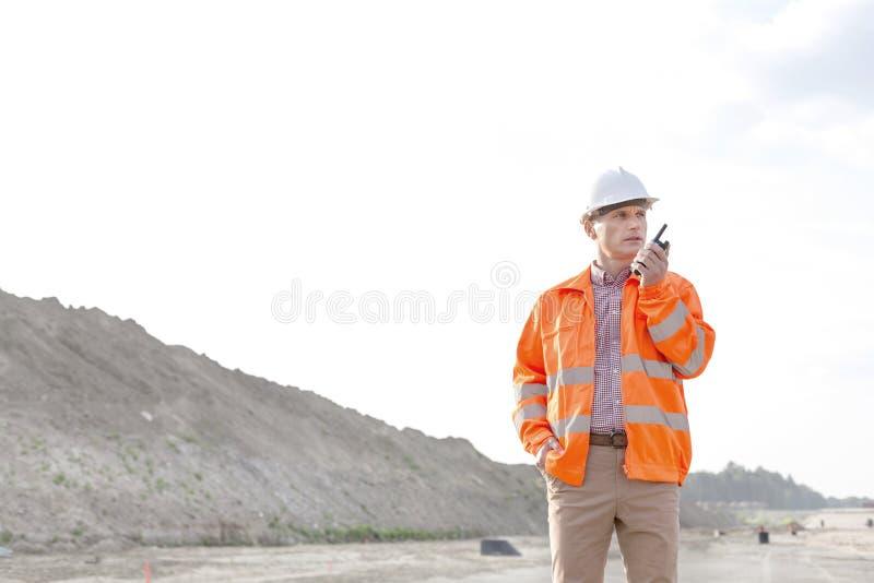 Βέβαιος αρσενικός επόπτης που χρησιμοποιεί walkie-talkie στο εργοτάξιο οικοδομής ενάντια στο σαφή ουρανό στοκ φωτογραφίες