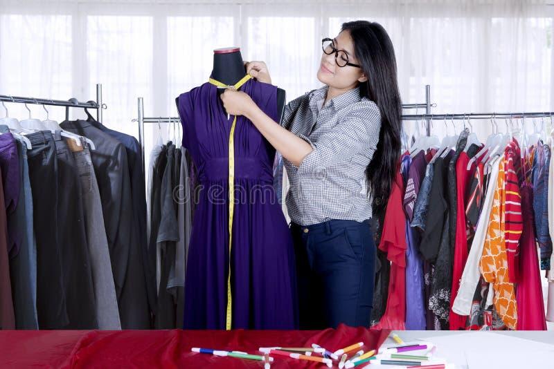 Βέβαιος ασιατικός σχεδιαστής μόδας που μετρά το ένδυμα στο πρότυπο μοδιστρών ` s στοκ φωτογραφία με δικαίωμα ελεύθερης χρήσης