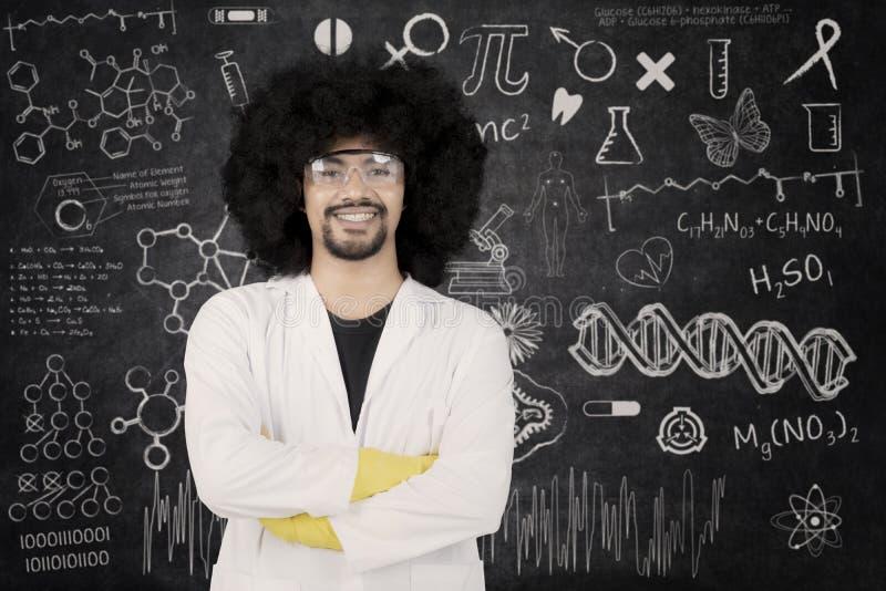 Βέβαιος επιστήμονας που στέκεται με τα όπλα που διασχίζονται στοκ φωτογραφία