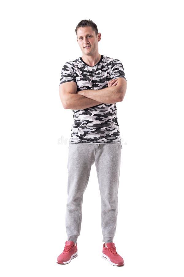 Βέβαιος επιτυχής μυϊκός αθλητικός τύπος στα sweatpants και το χαμόγελο πουκάμισων στρατού στοκ εικόνα με δικαίωμα ελεύθερης χρήσης