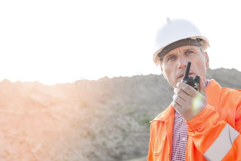 Βέβαιος επόπτης που χρησιμοποιεί walkie-talkie στο εργοτάξιο οικοδομής ενάντια στο σαφή ουρανό στοκ εικόνες