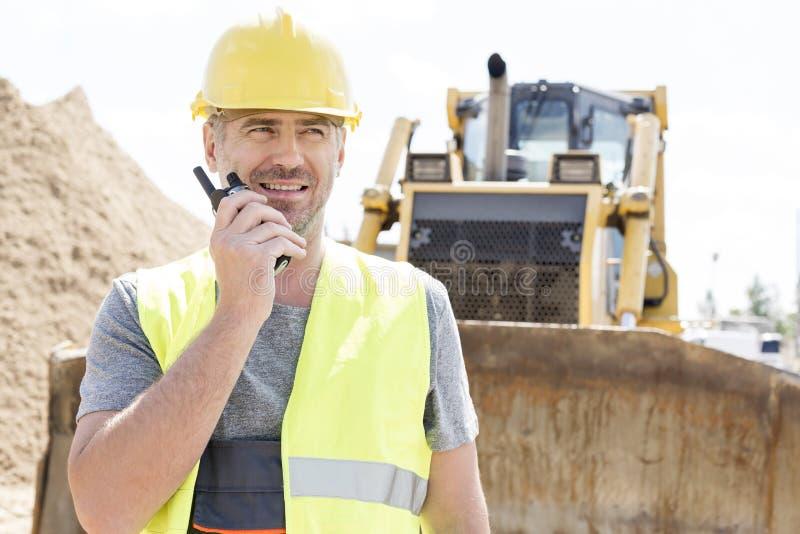 Βέβαιος επόπτης που χρησιμοποιεί walkie-talkie στο εργοτάξιο οικοδομής στοκ φωτογραφία με δικαίωμα ελεύθερης χρήσης