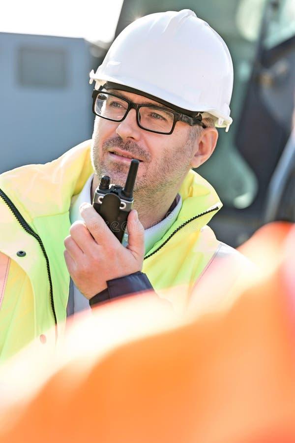 Βέβαιος επόπτης που χρησιμοποιεί walkie-talkie στο εργοτάξιο οικοδομής στοκ φωτογραφίες