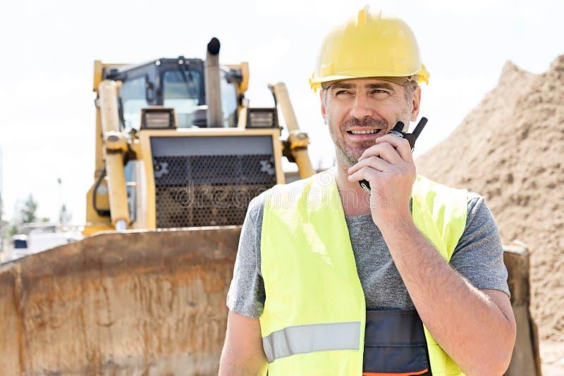 Βέβαιος επόπτης που χρησιμοποιεί walkie-talkie στο εργοτάξιο οικοδομής στοκ φωτογραφίες με δικαίωμα ελεύθερης χρήσης