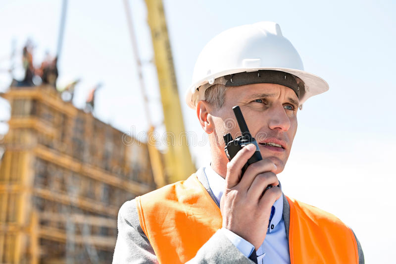 Βέβαιος επόπτης που χρησιμοποιεί walkie-talkie στο εργοτάξιο οικοδομής στοκ εικόνες με δικαίωμα ελεύθερης χρήσης