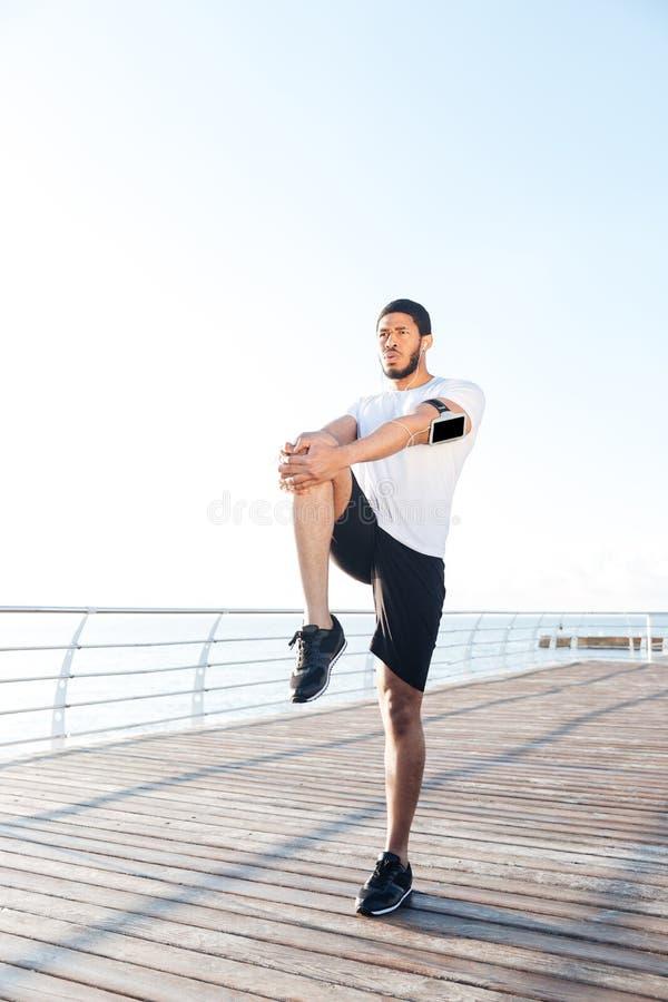Βέβαιος ελκυστικός αφρικανικός αθλητικός τύπος που κάνει τις ασκήσεις και που τεντώνει τα πόδια στοκ φωτογραφία με δικαίωμα ελεύθερης χρήσης