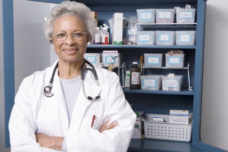 Βέβαιος θηλυκός γιατρός με τα χέρια που διπλώνονται στην κλινική στοκ εικόνα με δικαίωμα ελεύθερης χρήσης