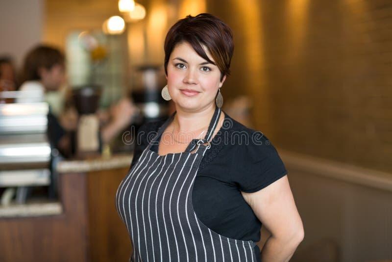 Βέβαιος θηλυκός ιδιοκτήτης που χαμογελά στην καφετέρια στοκ εικόνα