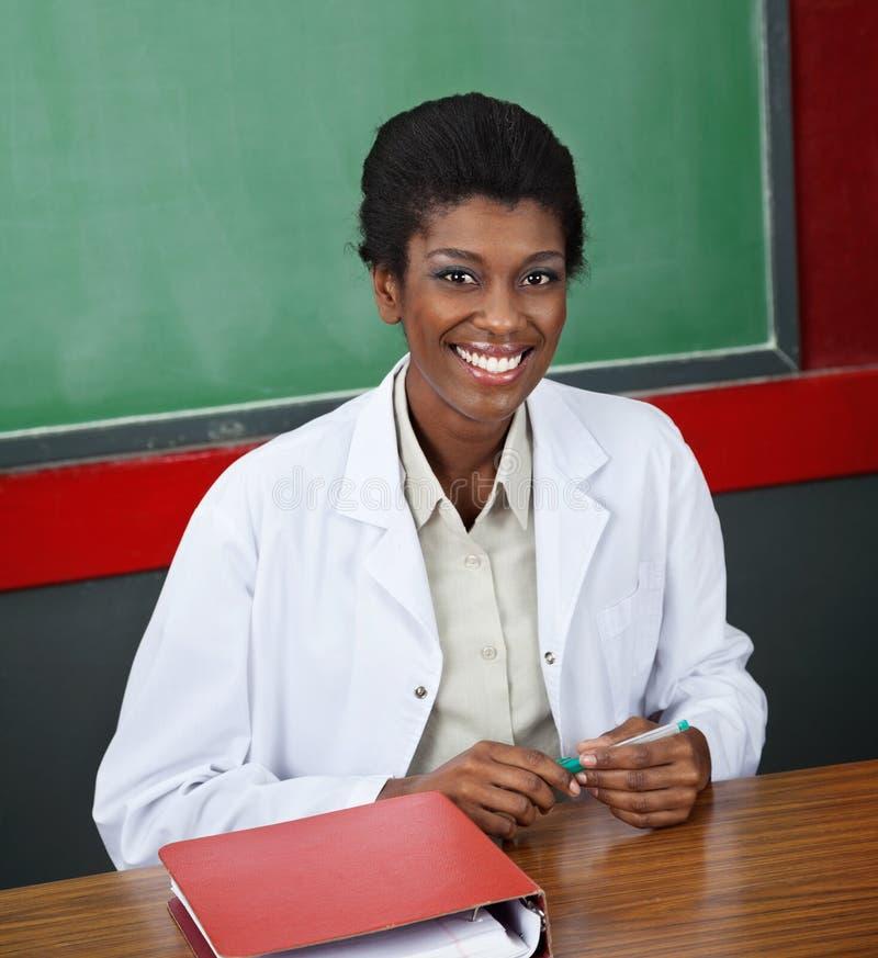 Βέβαιος θηλυκός καθηγητής Sitting στο γραφείο στοκ φωτογραφίες