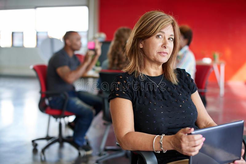 Βέβαιος θηλυκός σχεδιαστής που εργάζεται σε μια ψηφιακή ταμπλέτα στον κόκκινο δημιουργικό χώρο γραφείου στοκ εικόνα