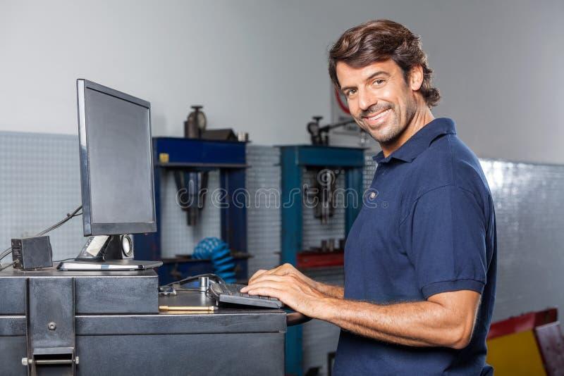 Βέβαιος μηχανικός χρησιμοποιώντας υπολογιστής στο κατάστημα επισκευής στοκ εικόνα