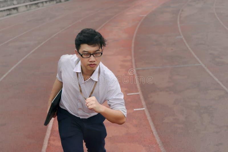 Βέβαιος νέος ασιατικός επιχειρηματίας με το έτοιμο τρέξιμο lap-top που διαβιβάζει στη διαδρομή φυλών διάγραμμα επιχειρησιακής ένν στοκ φωτογραφίες