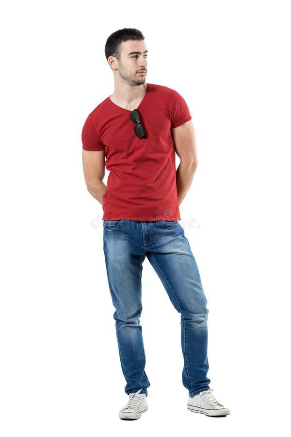 Βέβαιος νέος γόης με τα χέρια πίσω από την πλάτη που κοιτάζει μακριά στοκ φωτογραφία με δικαίωμα ελεύθερης χρήσης