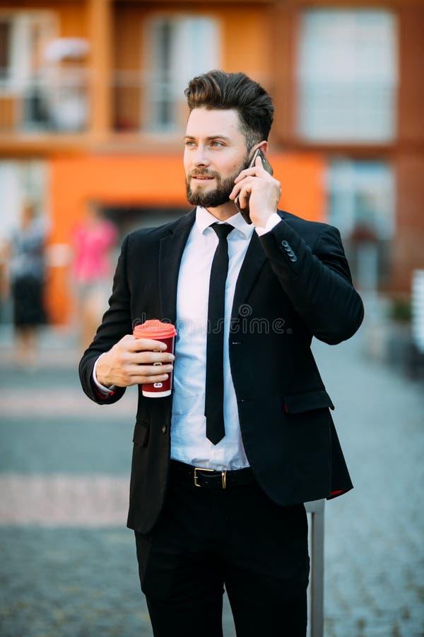 Βέβαιος νέος επιχειρηματίας χρησιμοποιώντας το τηλέφωνο κυττάρων και πίνοντας τον καφέ στην πόλη στοκ φωτογραφίες με δικαίωμα ελεύθερης χρήσης