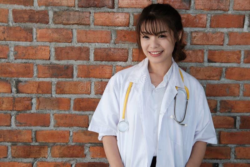 Βέβαιος νέος θηλυκός γιατρός που χαμογελά στη κάμερα Πορτρέτο του Μ στοκ εικόνες