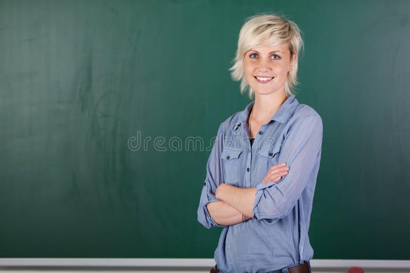 Βέβαιος νέος θηλυκός δάσκαλος μπροστά από τον πίνακα κιμωλίας στοκ φωτογραφίες