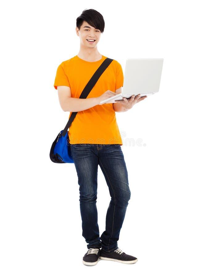 Βέβαιος νέος σπουδαστής που στέκεται και που χρησιμοποιεί το lap-top στοκ εικόνα