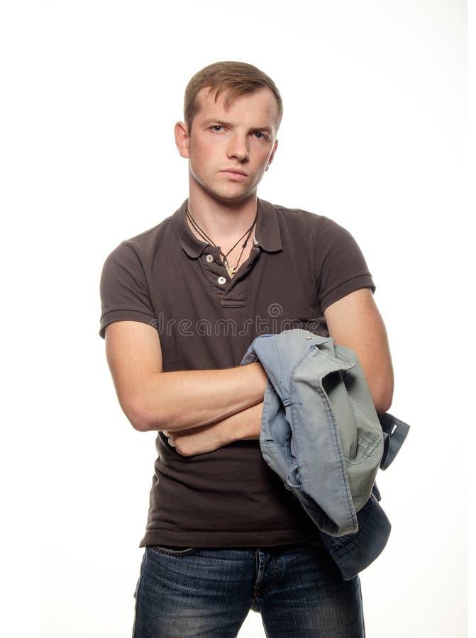 Βέβαιος νεαρός άνδρας με μια φανέλλα τζιν στα χέρια σε ένα άσπρο BA στοκ φωτογραφίες