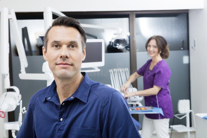 Βέβαιος οδοντίατρος με τη γυναίκα βοηθός που χαμογελά στην κλινική στοκ φωτογραφίες με δικαίωμα ελεύθερης χρήσης
