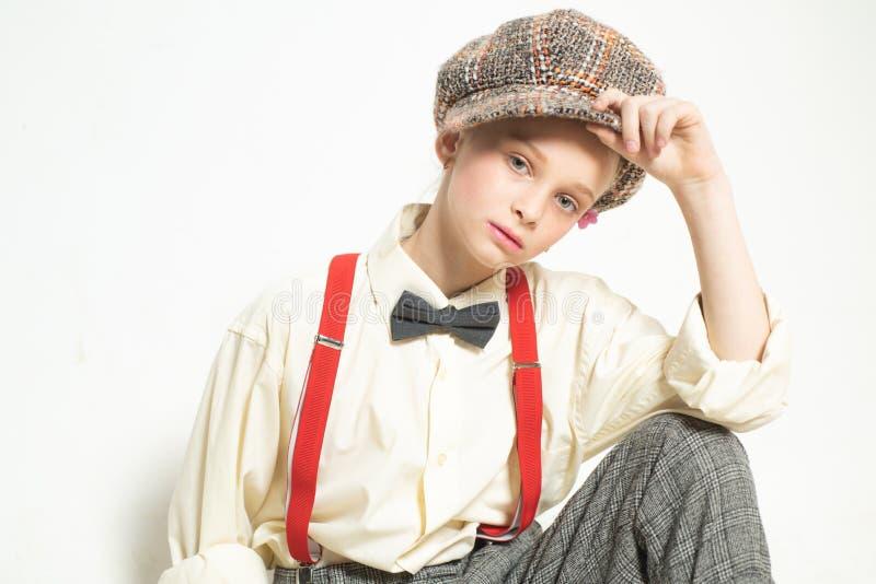 Βέβαιος στο ύφος της κορίτσι εφήβων στο αναδρομικό κοστούμι suspender και τόξων δεσμός E r στοκ φωτογραφία