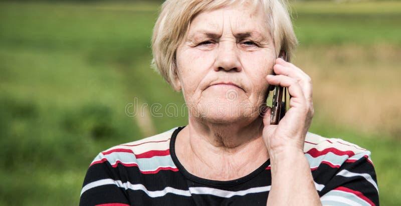 Βέβαιος φανείτε ώριμη ομιλία γυναικών σε ένα τηλέφωνο στοκ εικόνα