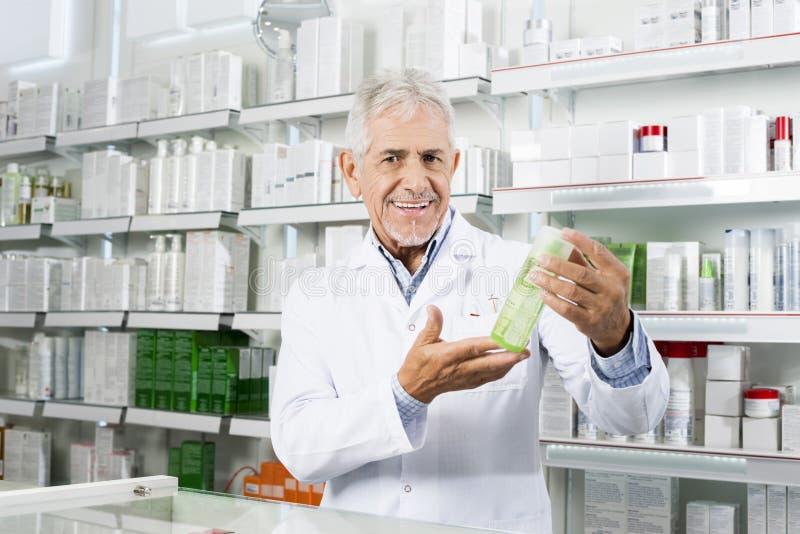 Βέβαιος φαρμακοποιός που χαμογελά ενώ προϊόν εκμετάλλευσης στο φαρμακείο στοκ εικόνες