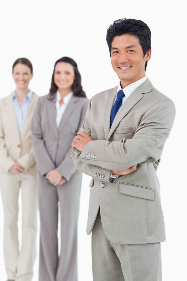 Βέβαιος χαμογελώντας επιχειρηματίας με τους υπαλλήλους του πίσω από τον στοκ εικόνες