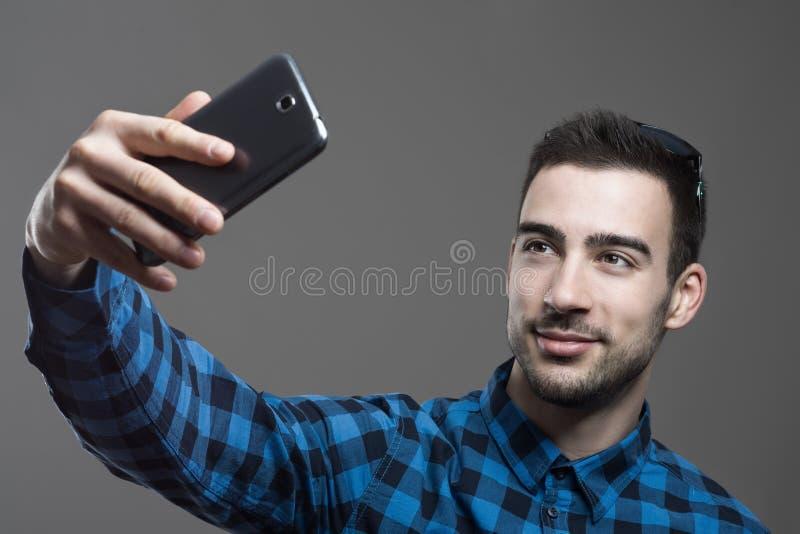 Βέβαιος flirty νεαρός άνδρας που παίρνει το υψηλό πορτρέτο γωνίας selfie στοκ εικόνα
