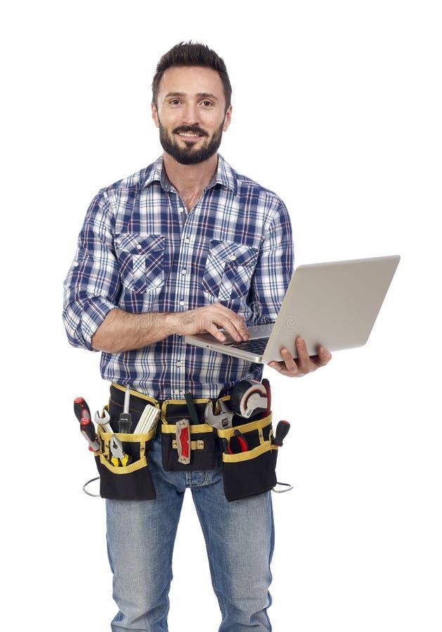 Βέβαιος handyman με το lap-top στοκ φωτογραφία