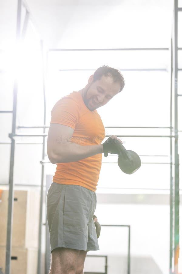 Βέβαιο άτομο που ανυψώνει kettlebell στη γυμναστική crossfit στοκ φωτογραφίες