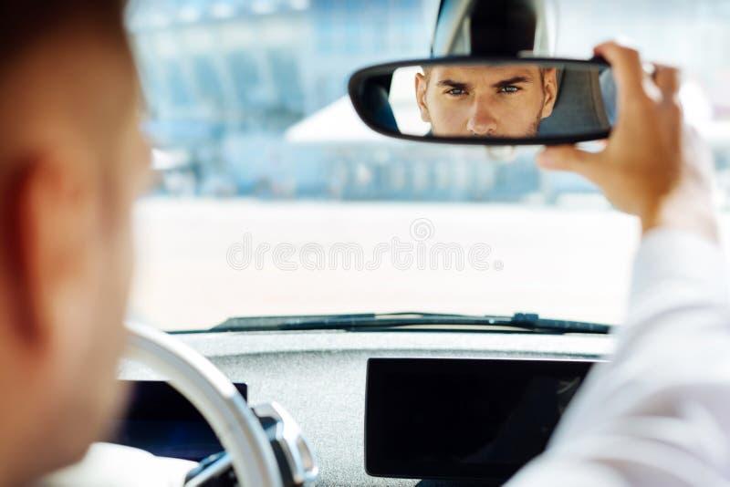 Βέβαιο έξυπνο άτομο που εξετάζει τον οπισθοσκόπο καθρέφτη στοκ εικόνα