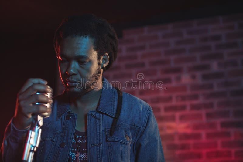 Βέβαιο αρσενικό μικρόφωνο εκμετάλλευσης τραγουδιστών στο νυχτερινό κέντρο διασκέδασης στοκ εικόνες με δικαίωμα ελεύθερης χρήσης