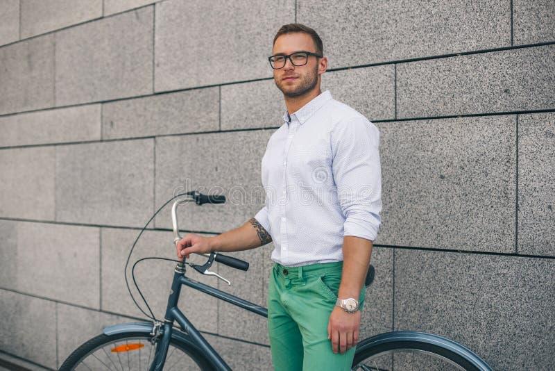 Βέβαιο επιχειρησιακό άτομο με το ποδήλατο Βέβαιο νέο όμορφο άτομο στο πουκάμισο στοκ εικόνες