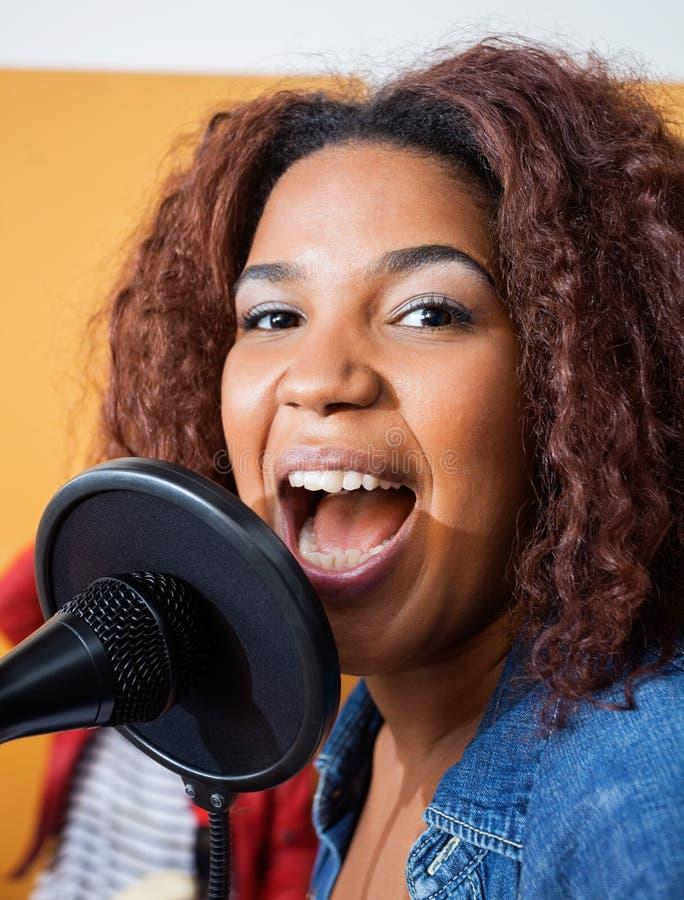 Βέβαιο νέο τραγούδι γυναικών στο στούντιο καταγραφής στοκ εικόνες