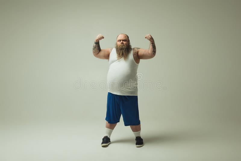 Βέβαιο παχύ άτομο που τεντώνει τους μυς του στοκ φωτογραφία με δικαίωμα ελεύθερης χρήσης