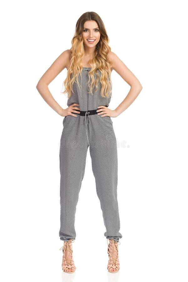 Βέβαιο πρότυπο μόδας χαμόγελου σε Jumpsuit και τα υψηλά τακούνια στοκ εικόνα με δικαίωμα ελεύθερης χρήσης