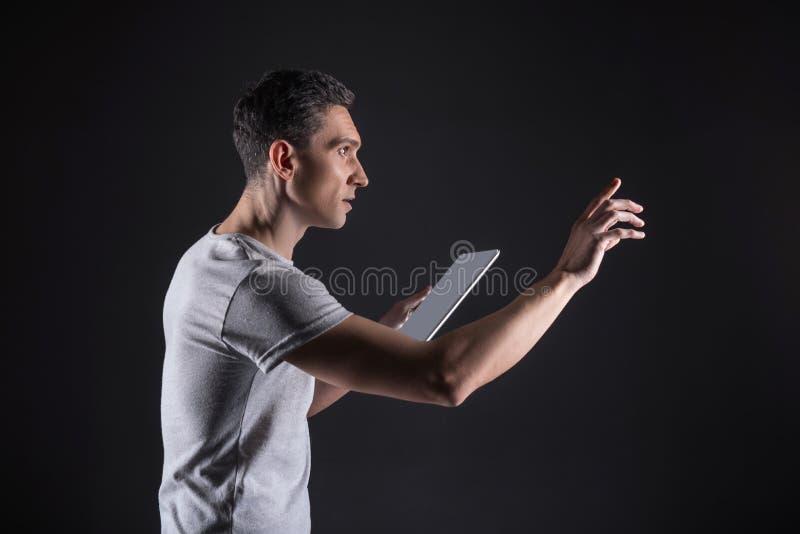 Βέβαιο όμορφο άτομο που εργάζεται με τις ψηφιακές συσκευές στοκ εικόνα