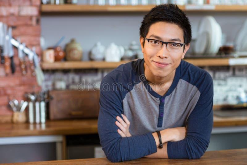 Βέβαιο όμορφο άτομο που στέκεται στον καφέ με τα όπλα που διασχίζονται στοκ φωτογραφία