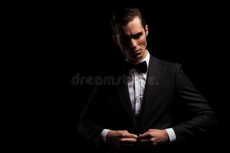 Βέβαιο όμορφο άτομο στη μαύρη τοποθέτηση στο σκοτεινό στούντιο στοκ φωτογραφία με δικαίωμα ελεύθερης χρήσης
