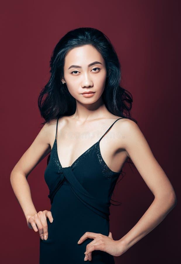 Βέβαιο όμορφο ασιατικό κορίτσι στο μαύρο φόρεμα, χέρια στα ισχία στοκ εικόνες