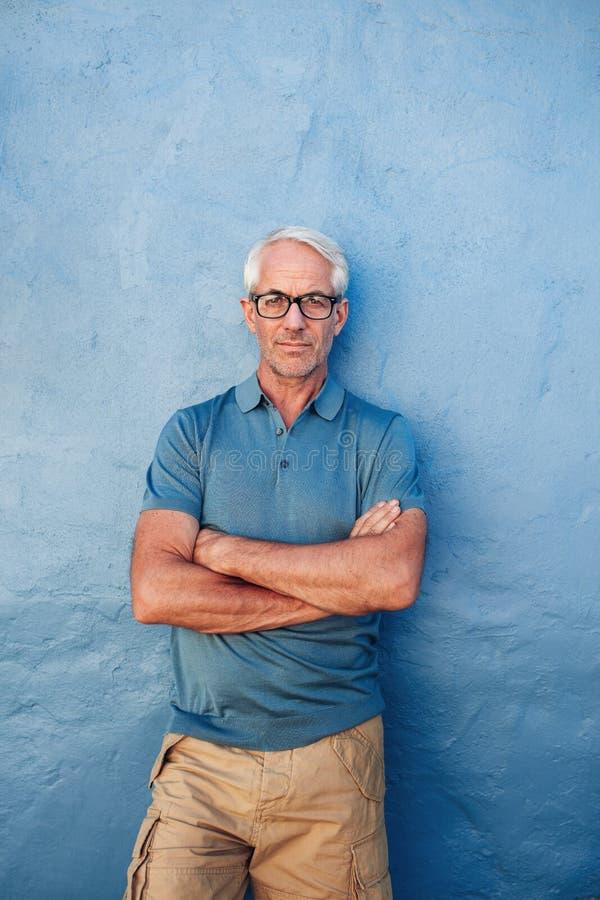 Βέβαιο ώριμο άτομο που στέκεται σε ένα μπλε κλίμα στοκ εικόνα με δικαίωμα ελεύθερης χρήσης