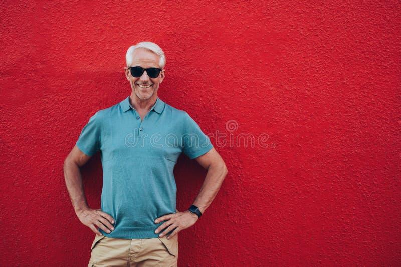 Βέβαιο ώριμο άτομο που στέκεται στο κόκκινο υπόβαθρο στοκ εικόνα