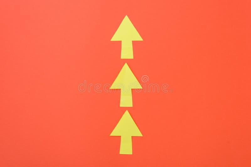 Βέλη μόνο μπροστινά Τρία βέλη σε μια κατεύθυνση Πορτοκαλί υπόβαθρο και φωτεινά κίτρινα βέλη στοκ εικόνες