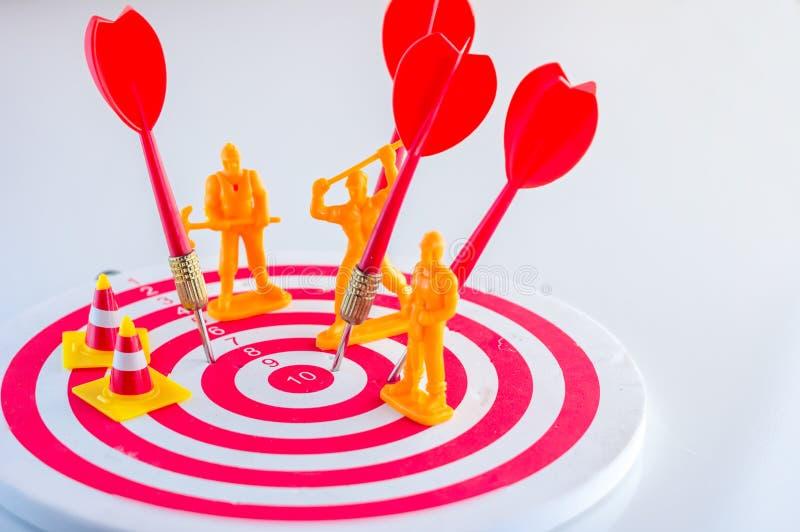 Βέλος βελών που χτυπά το κέντρο ενός στόχου με τον αριθμό εργατών στοκ εικόνα