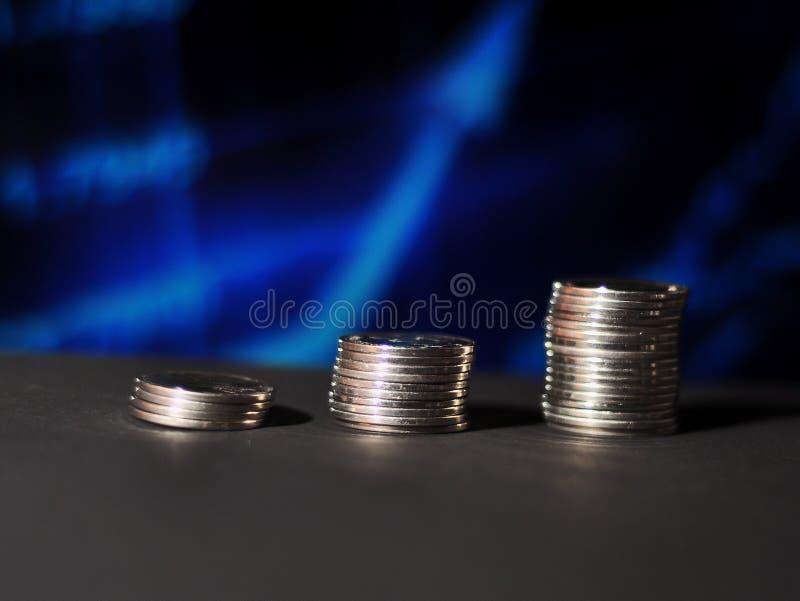Βήματα νομισμάτων με το μπλε γραφικό θολωμένο υπόβαθρο στοκ εικόνα