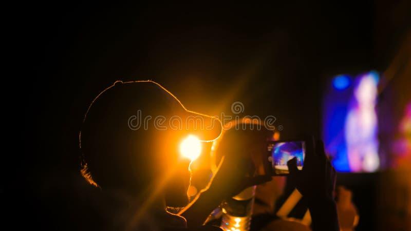 Βίντεο καταγραφής σκιαγραφιών ατόμων της συναυλίας ζωντανής μουσικής με το smartphone στοκ φωτογραφία