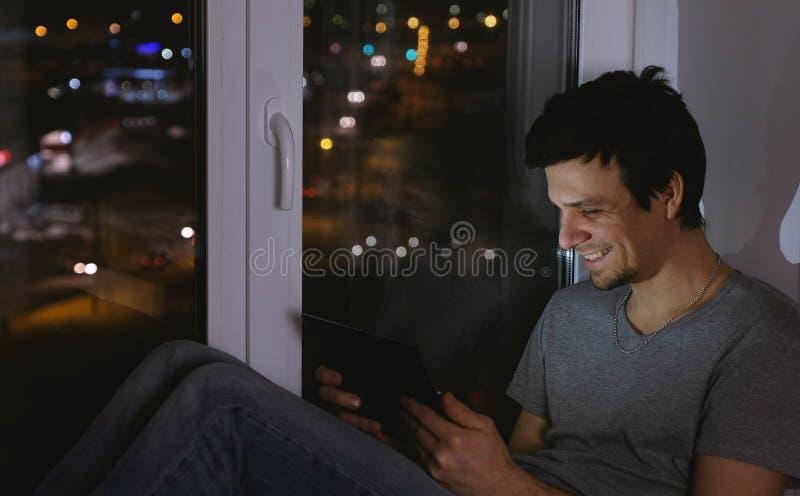 Βίντεο προσοχής ατόμων στο τηλέφωνο και γέλιο Κάθισμα στο windowsill στη σκοτεινή νύχτα στοκ φωτογραφία