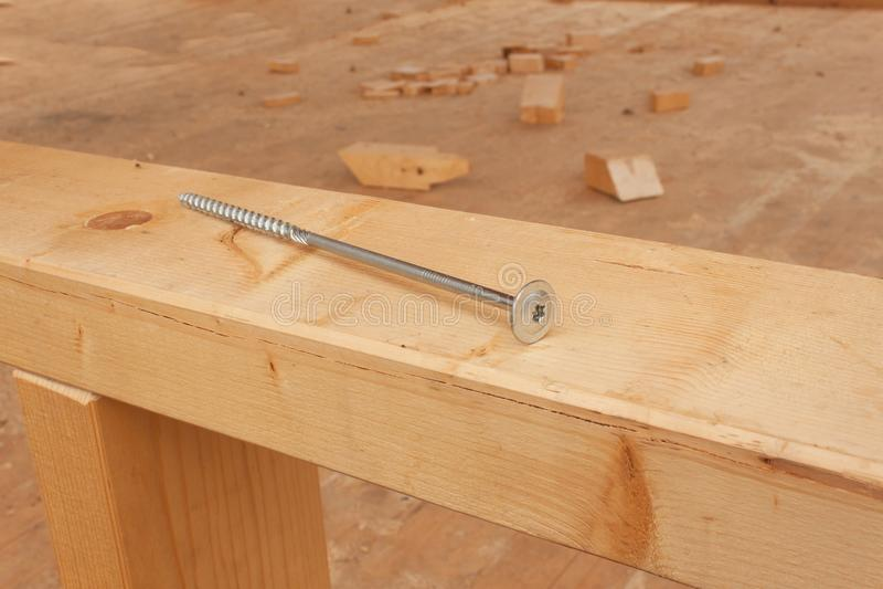 Βίδες και καρφιά για να χτίσει ένα ξύλινο σπίτι Ενώνοντας ξύλινες ακτίνες Οικοδομές στοκ φωτογραφίες