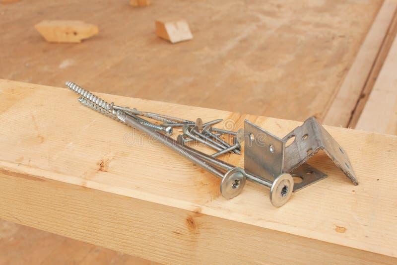 Βίδες και καρφιά για να χτίσει ένα ξύλινο σπίτι Ενώνοντας ξύλινες ακτίνες Οικοδομές στοκ εικόνα με δικαίωμα ελεύθερης χρήσης